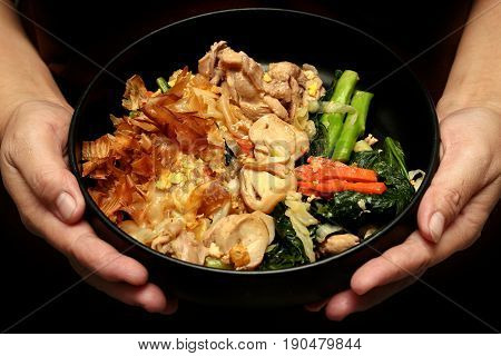 Thai popular food Fried big noodle with marinated pork in soy sauce and vegetable call Sen Yai Pad Cee Oue in Thai.