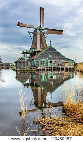 Wooden Windmill Zaanse Schans Old Windmill Village Countryside Holland Netherlands. Working windmills from the 16th to 18th century on the River Zaan. Windmills powered industries in Holland such as ship builidng vegetable oil production.