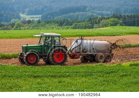 Tractor With Trailer Fertilizing Field With Natural Manure