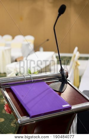 Book speed on podium with abstract blur photo of conference hall or seminar room in background. Business seminar concept.