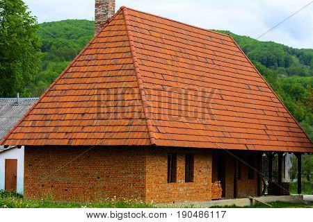 Unfinished house with a tiled roof in the village