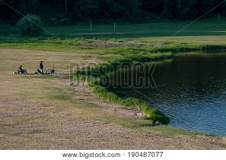 Man fishing from the shore of lake early morning