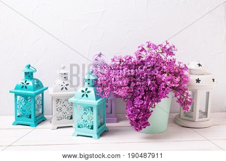 Lilac flowers in box and brigh lanterns on white wooden background against grey wall. Selective focus. Place for text.