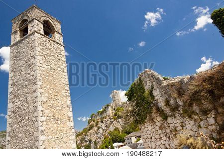 Clock tower - Pocitelj Bosnia and Herzegovina. In background old fortification.