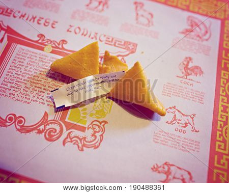 Broken fortune cookie with quote about making opportunites against background of classic chinese restaurant background
