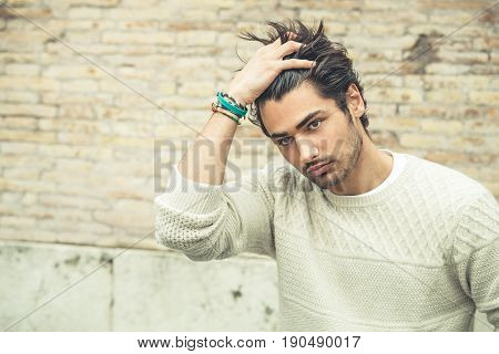 Cool young man fashion model, hairstyle. A beautiful young boy passes his hand through his hair. Slight beard. The boy wears a white sweater, outdoors.