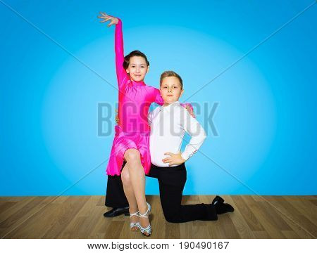 The young boy and girl posing at dance studio on blue. The ballroom dancing concept