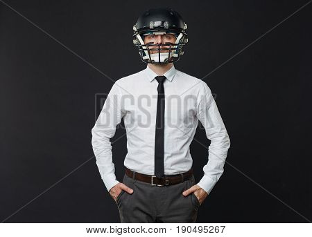 Portrait of confident mid adult businessman wearing American football helmet while standing with his hands in pockets against black background