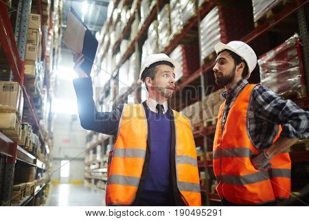 Two workers of storehouse discussing goods quality