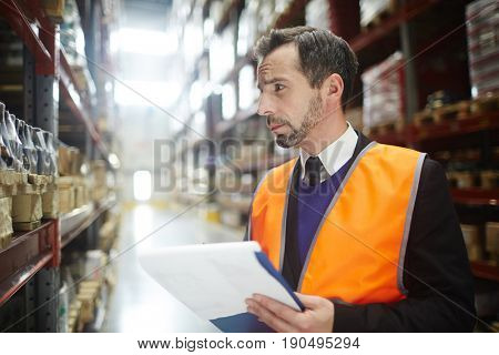 Young man making list of goods in storehouse