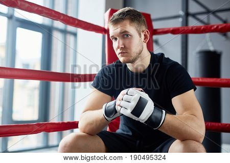 Portrait of young man posing in boxing ring sitting on floor and looking at camera looking at camera with confidence