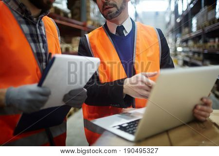 Storehouse worker explaining data in laptop to his colleague