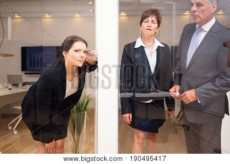 businesswoman eavesdropping on her superiors in the office