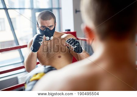 Portrait of young boxer wearing endurance training mask fighting with opponent in boxing ring