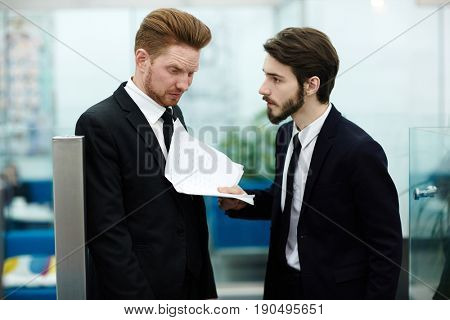 Dissatisfied employer showing papers to one of managers