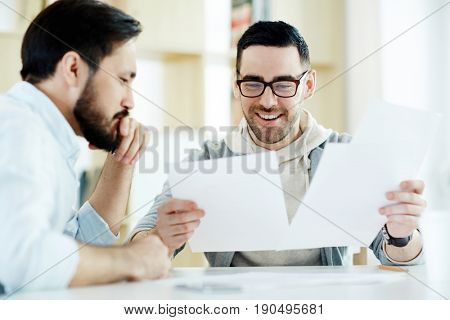 Young economists discussing documents at work