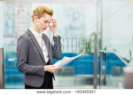 Busy female reading business papers at work