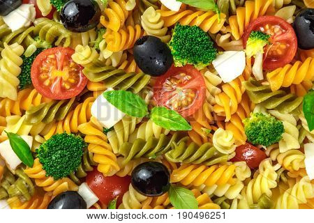 A closeup photo of a pasta salad. Rotini of various colours, fresh green basil leaves, black olives, mozzarella cheese slices, broccoli, and cherry tomatoes