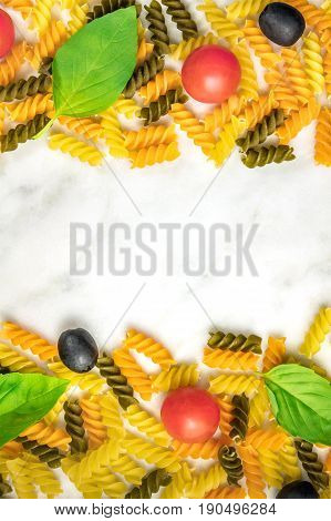 Pasta salad ingredients on white marble with a place for text. Rotini, cherry tomatoes, fresh basil leaves, and black olives, forming a frame for copy space