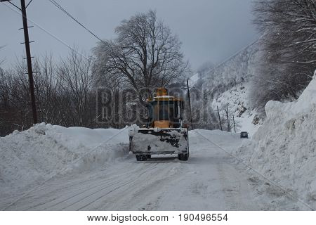 Winter landscape mountains snow cleaning machine. Wheel loader machine tractor unloading snow during municipal works crews. Tractor loader cleans snow after a snowfall