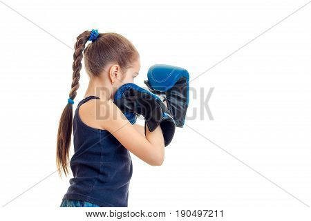 little girl in blue sports gloves practicing boxing isolated on white background