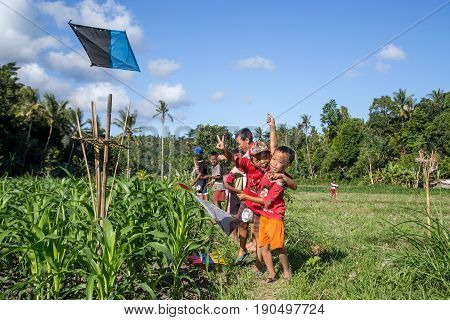 Bali, Indonesia - July 07, 2015: Balinese kids playing with kites in the fields