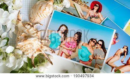 Many bright colored photos of girls in swimsuits and hats on a table with seashells and flowers. Memories of a vacation at sea