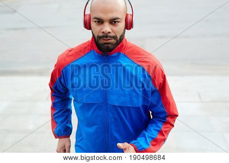 Young sprinter in activewear training outdoors