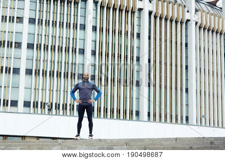 Young athlete standing against modern building