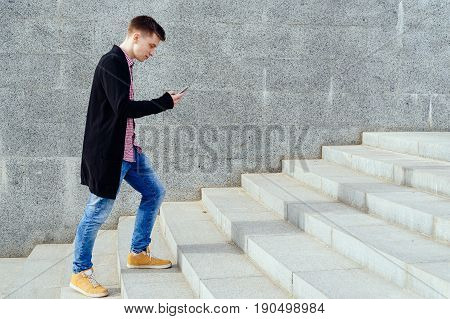 Stylish Young Man In Plaid Shirt And Jeans Walking Up Stairs And Using Smartphone Outdoors. Student