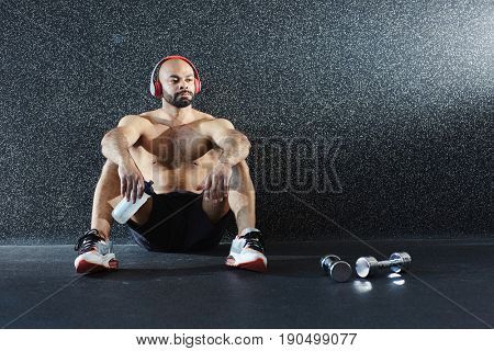Portrait of strong muscular man sitting on floor drinking water and listening to music in big headphones while resting after intense strength workout in gym
