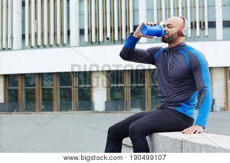 Thirsty runner drinking water from plastic bottle