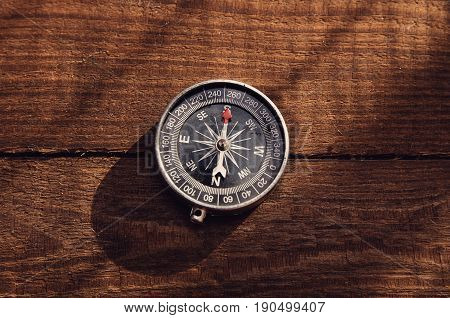 Hand compass rests on a wooden table
