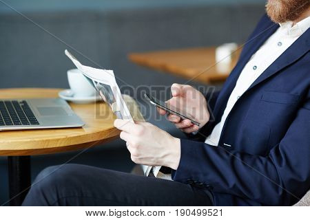 Employer with newspaper and smartphone messaging at break