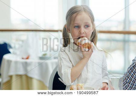 Little girl eating fresh crusty homemade croissant