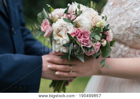Beautiful wedding bouquet of white and pink peony in bride's and groom's hands in blur close up