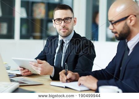 Professional trader with touchpad looking at camera by workplace