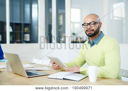 Young analyst with touchpad browsing at workplace