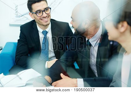 Happy businessman listening to co-worker during conversation