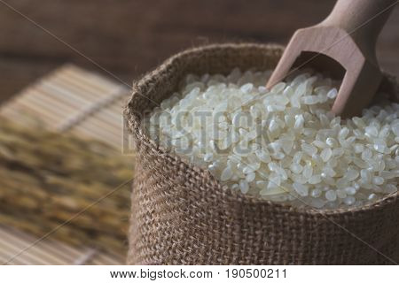 Macro concept of Japanese rice. Close up on gunny sack filled with Japanese rice. Background or wallpaper of Japanese rice in gunny sack on bamboo sushi mat with copy space. Vintage style bag filled with Japanese rice.
