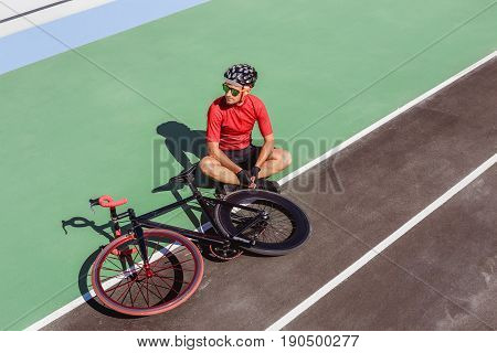 Athlete with a black bicycle at velodrome. Professional sports man in a red T-shirt and helmet.