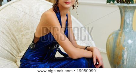 Young Beautiful Slim Brunette Girl In Long Blue Dress With Open Shoulders And Decollete Sitting With