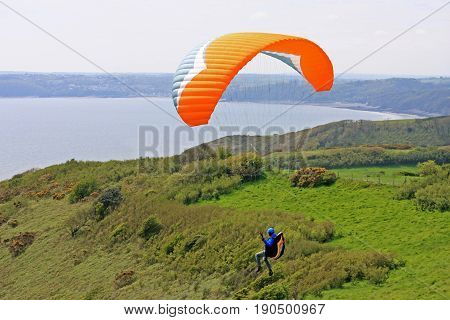 Paraglider flying above the coast of Cornwall