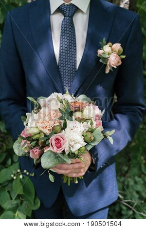 Beautiful Lush Wedding Bouquet Of White And Pink Peony And Roses In Groom's Hands. Groom In Suit Wit