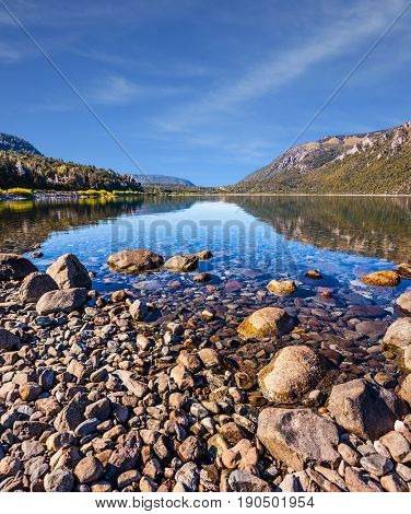 Lake with a stony pebble bottom at the famous resort of Bariloche. Picturesque summer in Argentina. The concept of exotic and extreme tourism