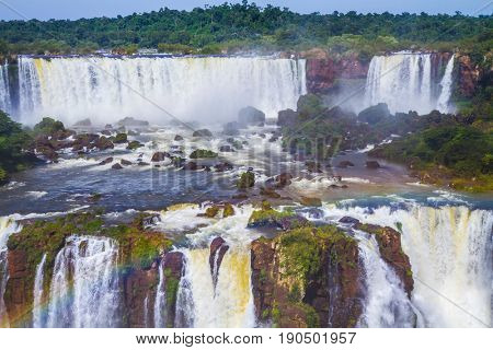 Waterfalls from Iguazu Falls. Powerful two-stage waterfall creates a watery dust and a rainbow. The concept of exotic and extreme tourism