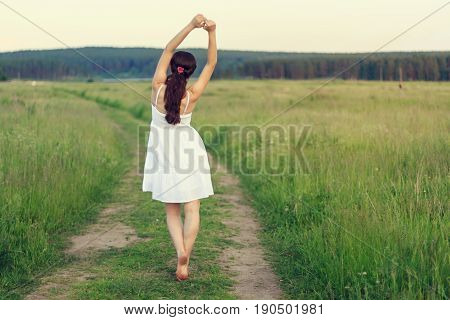 Young woman walking on a rural footpath while enjoying nature.