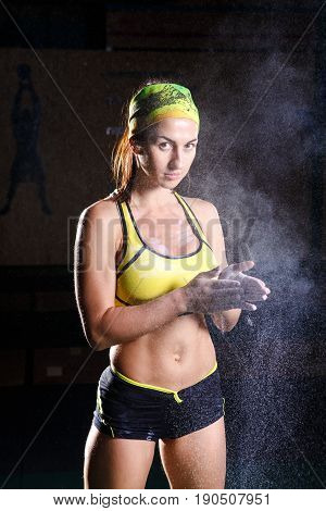Female Fitness Model Clapping Hands With Talc Powder In A Gym Just Before Doing Excersis.
