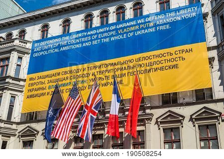 Berlin Germany - May 28 2017: Flags of Ukraine NATO USA Great Britain France former USSR on the wall of the Haus am Checkpoint Charlie museum as solidarity with Ukraine in Berlin Germany. Banner against Russian aggression in Ukraine.