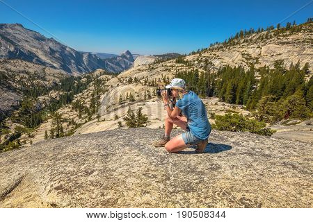 Travel photographer takes shot of north side Half Dome on Olmsted Point. Tioga Road in Yosemite National Park, California, USA. Nature photographer taking pictures outdoors during hiking trip.